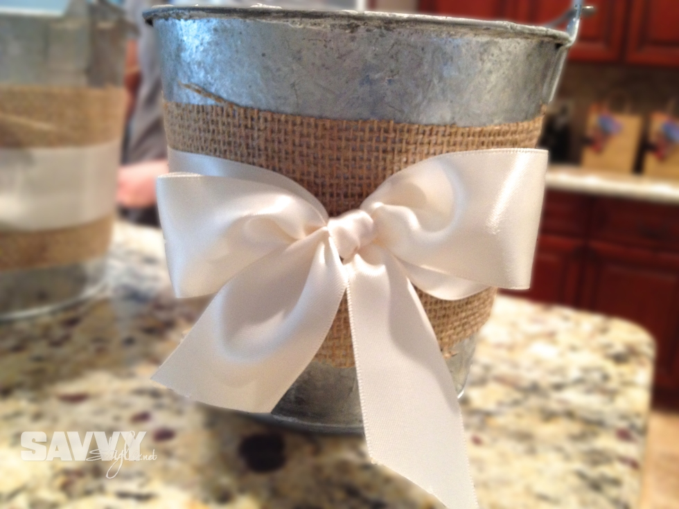 Burlap cut and hot glued to bucket, secured with ivory ribbon.
